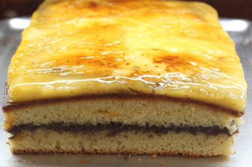 Coca de llanda rellena de chocolate y cubierta de yema tostada